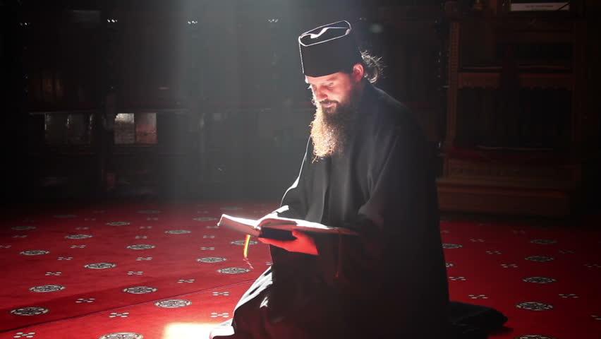 Monah rugându-se în Biserică